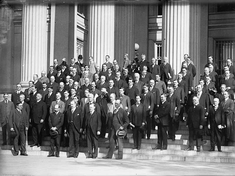 Federal Reserve governors stand with bankers on the steps of a building.