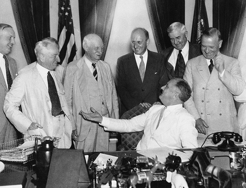 President Roosevelt chats with various politicians and administration officials as he signs the Banking Act of 1935.