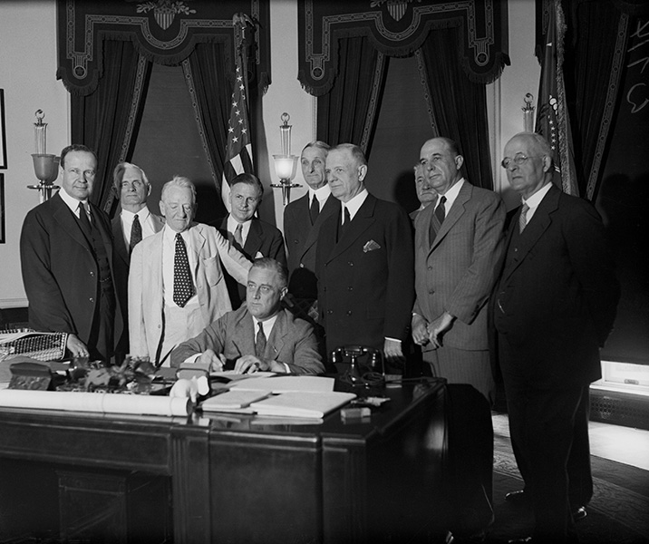 "President Roosevelt signs the Glass-Steagall Act alongside the bill""s co-sponsors, Senator Carter Glass and Representative Henry Steagall, and others."