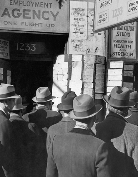 Men study the announcement of jobs at an employment agency during the Great Depression.