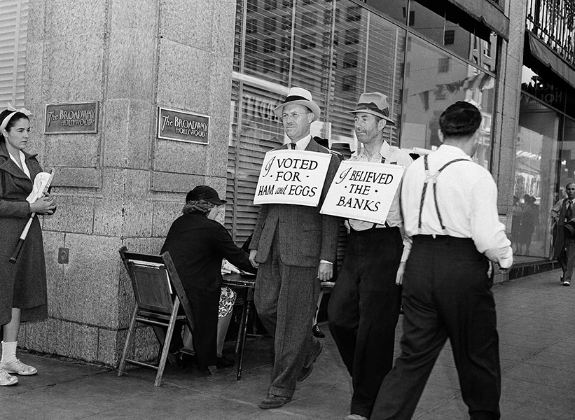 "Men wearing sandwich boards reading ""I voted for ham and eggs"" and ""I believed the banks"" walk down a Los Angeles street."