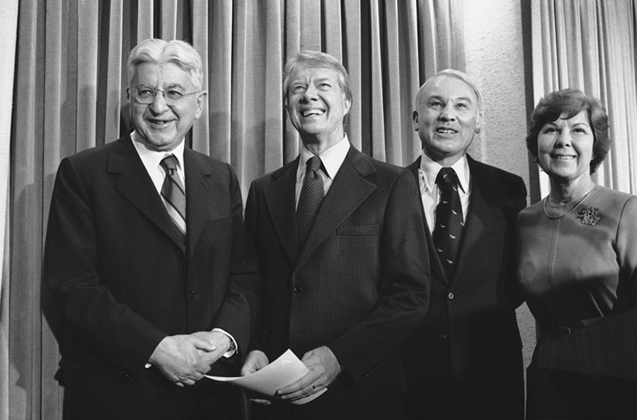 Arthur Burns, Jimmy Carter, and G. William Miller smile following the announcement of Miller to replace Burns as Chairman of the Federal Reserve Board.