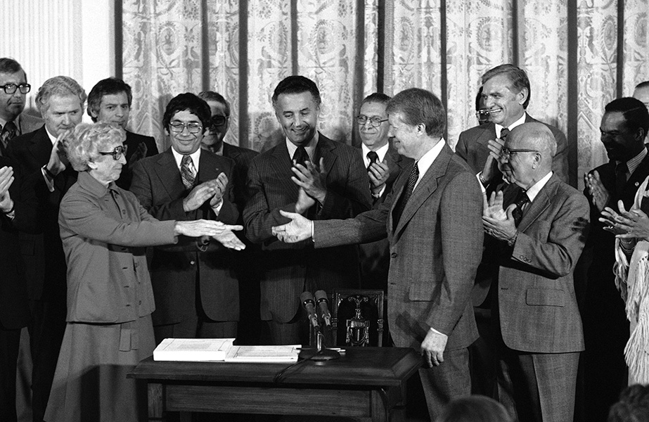 Senator Muriel Humphrey gives President Carter her hands to shake after Carter signed the Humphrey-Hawkins Bill into law.  Representative Augustus Hawkins, co-sponsor of the bill, is pictured to the right.