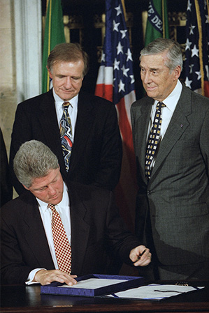 President Clinton signs the Interstate Banking and Branching Efficiency Act of 1994 as Senate Banking Committee Chairman Don Riegle and Treasury Secretary Lloyd Bentson look on.