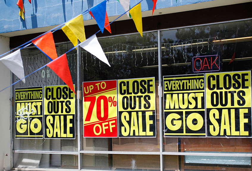 Store closing signs are posted in the windows of a furniture store in San Jose, California during the Great Recession.