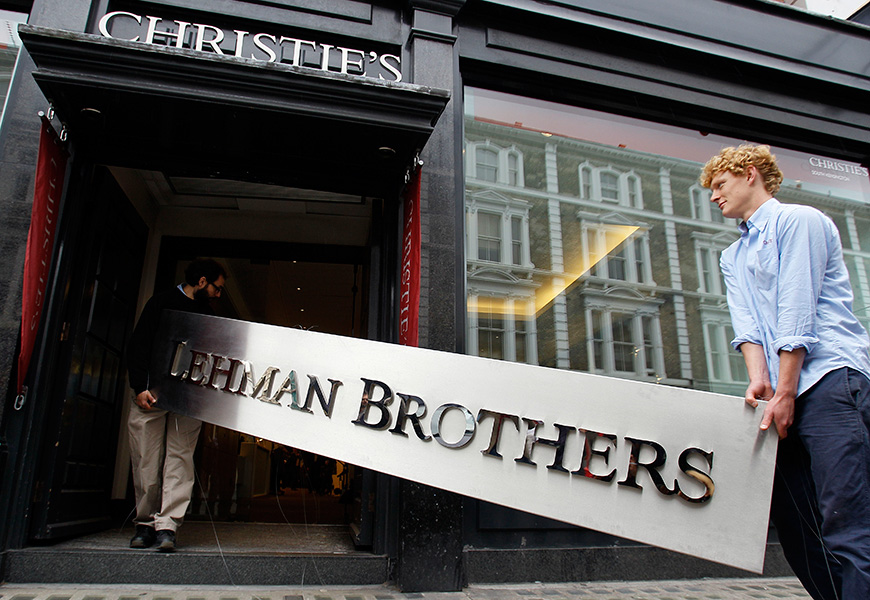 Two men carry the Lehman Brother's corporate sign to an auction house in London.
