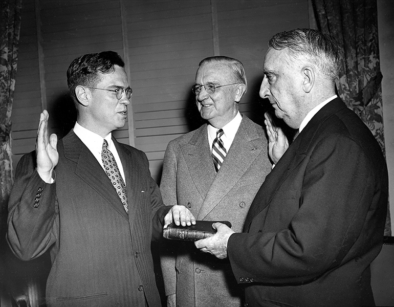 William McChesney Martin is sworn in as Chairman of the Federal Reserve Board of Governors by Chief Justice Fred Vinson, as his predecessor, Thomas B. McCabe, looks on.