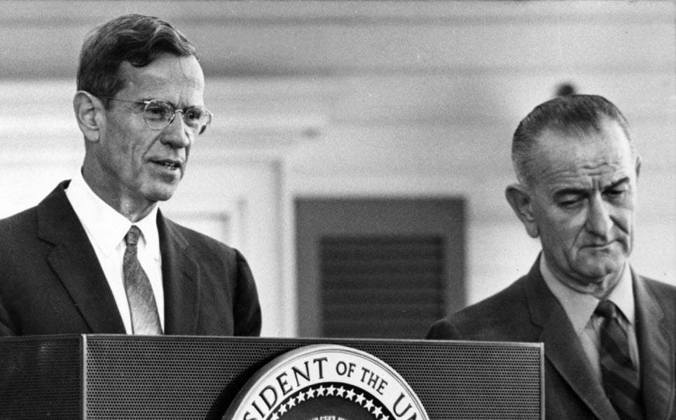 Federal Reserve Board Chairman William McChesney Martin, pictured beside President Lyndon Johnson, discusses the Board's action on raising the discount rate at a December 1965 news conference.