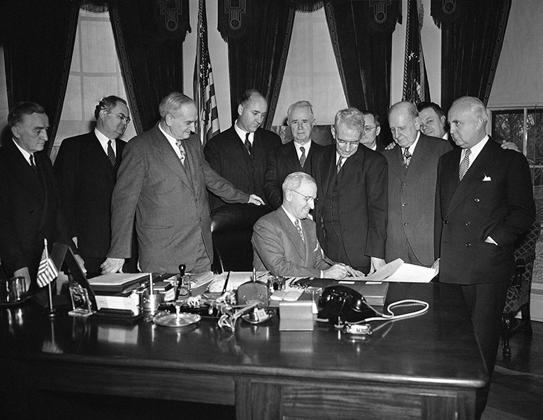"President Harry Truman signs the Employment Act of 1946, which Congress passed as a compromise for his so-called ""full employment"" legislation."