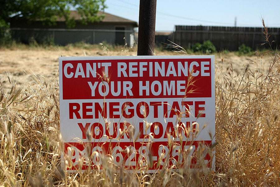 A sign advertising refinancing services is posted in a vacant lot April 29, 2008, in Stockton, California.